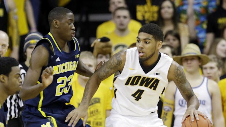 Iowa guard Devyn Marble, right, looks to drive past Michigan guard Caris LeVert (23) during the first half of an NCAA college basketball game, Saturday, Feb. 8, 2014, in Iowa City, Iowa