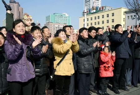 """North Koreans watching a huge screen broadcasting an official announcement that the country """"successfully"""" put an Earth observation satellite into orbit, calling it an """"epoch-making"""" achievement, applaud in Pyongyang"""