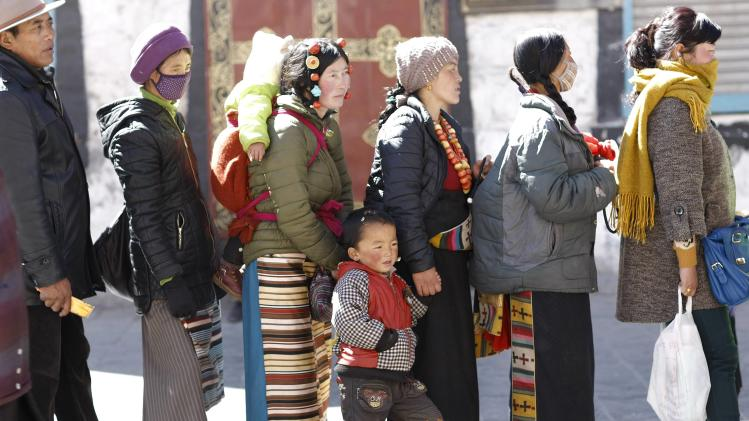 A boy holds his mother's hand as they queue to get in the Jokhang Monastery in Lhasa