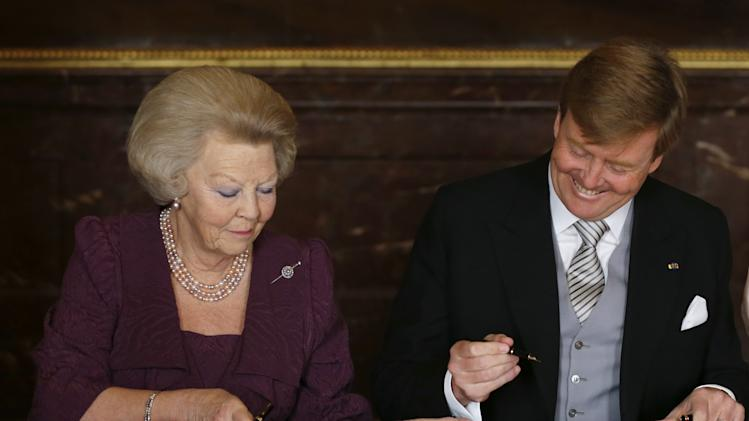 Dutch Princess Beatrix, left, gives to her son, King Willem-Alexander, the Act of Abdication which she signed to end her reign as Monarch in the Mozeszaal or Mozes hall of the Royal Palace in Amsterdam, The Netherlands, Tuesday April 30, 2013. Around a million people are expected to descend on the Dutch capital for a huge street party to celebrate the first new Dutch monarch in 33 years. (AP Photo/Bart Maat, pool)