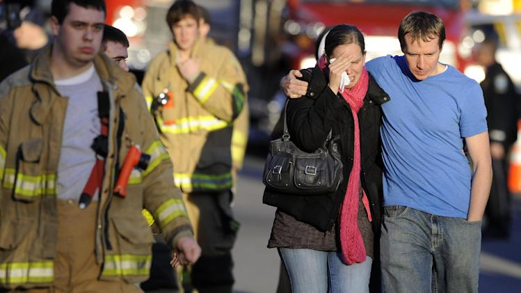 Robert and Alissa Parker, at right, leave a firehouse staging area following a shooting at the Sandy Hook Elementary School in Newtown, Conn., where authorities say a gunman opened fire, killing 26 children and adults at the school, including the Parkers' daughter Emilie Parker, 6, Friday, Dec. 14, 2012. (AP Photo/Jessica Hill)