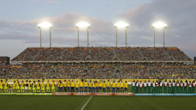 Brazil's team stands on the gold medal podium, center, alongside Mexico on the bronze podium, right, and Colombia on the silver podium after Brazil defeated Colombia in the gold medal Pan Am Games soccer match Saturday, July 25, 2015, in Hamilton, Ontario. (AP Photo/Gregory Bull)