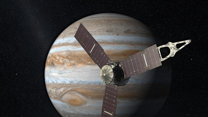 FILE - This 2010 artist's rendering depicts NASA's Juno spacecraft with Jupiter in the background. NASA's Jupiter-bound spacecraft will swing by Earth for one last visit Wednesday Oct. 9, 2013 before speeding to the outer solar system. Wednesday's flyby allows the Juno spacecraft to gather the momentum it needs to arrive at Jupiter in 2016. (AP Photo/NASA/JPL, File)