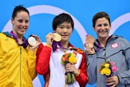 China's Ye Shiwen (C) poses on the podium with the gold medal flanked by silver medalist Australia's Alicia Coutts (L) and bronze medalist US swimmer Caitlin Leverenz (R) after winning the women's 200m individual medley final during the swimming event at the London 2012 Olympic Games