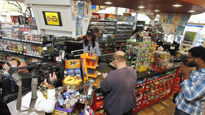 In this Nov. 29, 2012 file photo, members of the media document store cashier Tanice Stefanich helping a customer at a 4 Sons Food Store where one of the winning tickets in the $579.9 million Powerball jackpot was purchased in Fountain Hills, Ariz.  When two winning tickets for a record Powerball jackpot were claimed last month, the world focused on the winners. One, from Missouri, showed up at the newsconference, while the other, in Arizona, chose to remain anonymous. Releasing information on the lottery winners reflects a broader debate playing out in state Legislatures and lottery offices nationwide: Should the winners' names be made public?(AP Photo/Ross D. Franklin, file)