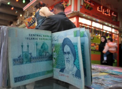 "An Iraqi money dealer counts Iranian rial bank notes bearing a portrait of the founder of the Islamic Republic of Iran, the late Ayatollah Ruhollah Khomeini, at an exchange office in Baghdad. Iran's currency has slid to a new record low against the dollar, with the central bank saying it was trying to manage the plunge amid an ""economic war with the world."""