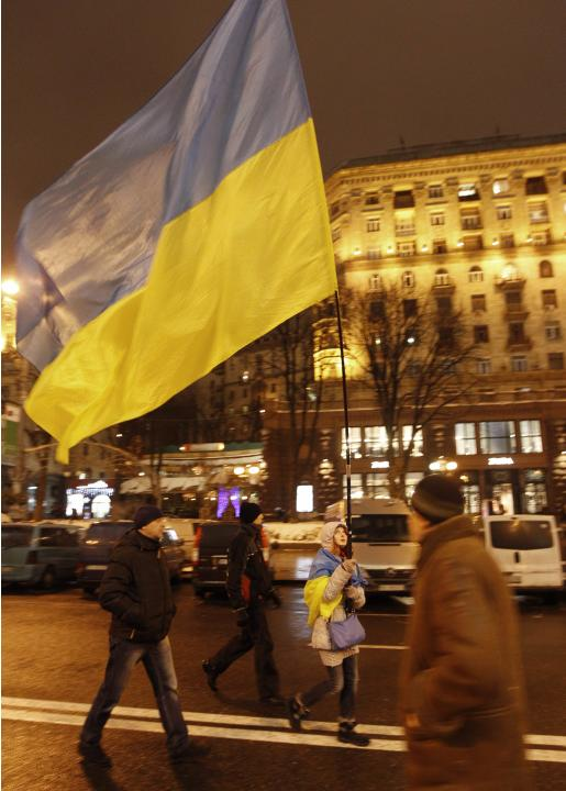 A pro-European integration protester holds a Ukrainian national flag as she walks along the main avenue in Kiev