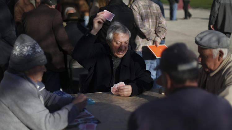 In this photo taken on February 19, 2013, retired men play cards in a public square in Lisbon,.Taxes and cuts in previous years had already cut pensioners income by 20 percent as the government looked to cut the national debt. (AP Photo/Francisco Seco)