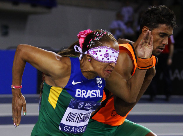 Brazil's Terezinha Guilhermina runs alongside her guide in the women's 60m T11/12 event during the British Athletics International Match at the Emirates Stadium in Glasgow