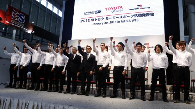 Toyota Motor Corp President Toyoda raises his hand with racers of Toyota motor sports teams during a news conference to announce its return to the FIA World Rally Championship in 2017, in Tokyo