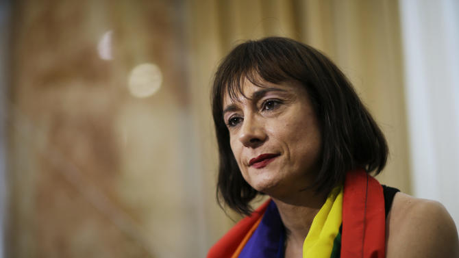 """Vladimir Luxuria, a former Communist lawmaker in the Italian parliament and prominent crusader for transgender rights, sits for an interview, Monday, Feb. 17, 2014, in central Sochi, Russia, home of the 2014 Winter Olympics. Luxuria said she was detained by police at the Olympics after being stopped while carrying a rainbow flag that read in Russian: """"Gay is OK."""" Police on Monday denied this happened. (AP Photo/David Goldman)"""