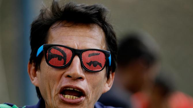 A supporter of Venezuela's President Hugo Chavez wears sunglasses decorated with the eyes of Venezuela's President Hugo Chavez at a rally in Caracas, Venezuela, Wednesday, Jan. 23, 2013. The cult of personality that Chavez long nurtured has been flourishing like never before as he confronts an increasingly difficult struggle against the mysterious cancer that afflicts him. The iconic eyes-only design sends a message that he is always watching and still with his adoring constituents. (AP Photo/Fernando Llano)
