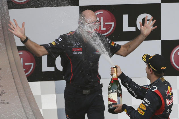 Red Bull Formula One driver Vettel sprays champagne on Red Bull's technical chief Newey during the podium ceremony after the South Korean F1 Grand Prix at the Korea International Circuit in Yeongam