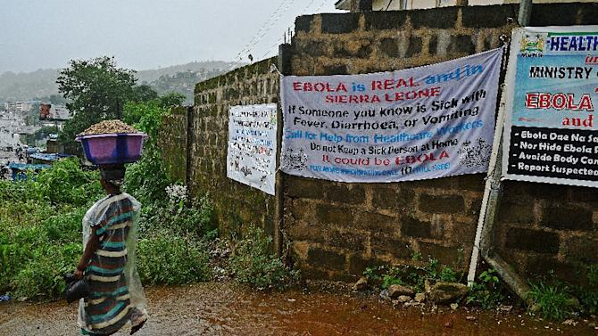 A woman walks past signs warning of Ebola in Freetown, an area which has been hit hard with the spread of the deadly virus, on August 13, 2014