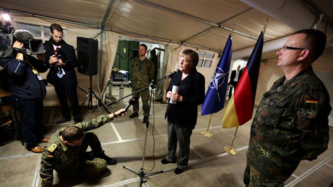 German Chancellor Angela Merkel speaks while she visits German soldiers in Kahramanmaras, southeastern Turkey,  Sunday Feb. 24, 2013. German Chancellor Angela Merkel is visiting German troops deployed to operate Patriot missile batteries in Turkey. The Patriots were sent to Turkey, a NATO member, to protect it from spillover from Syria's civil war. Merkel's two-day visit comes as Turkey grows increasingly frustrated over the slow progress in its bid for European Union membership. Before arriving Sunday, Merkel said she backs opening a new chapter in those stalled talks, despite being skeptical about Turkey's accession. The chancellor's first stop was Kahramanmaras, some 100 kilometers (60 miles) from the Syrian border, where some 300 German troops are manning two out of six NATO-deployed anti-missile batteries.  (AP Photo/dpa, Kay Nietfeld)