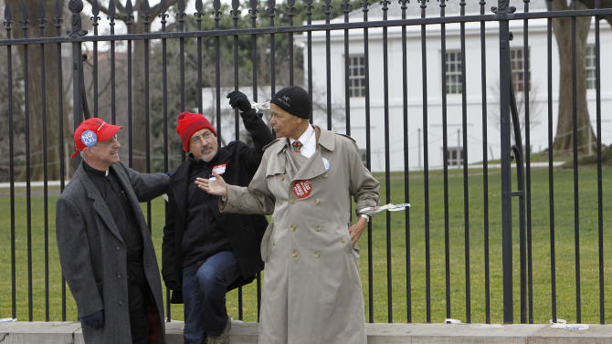 Civil Rights leader Julian Bond, right, talks with Chesapeake Climate Action Network Executive Director, Mike Tidwell, center, and another activist as they are chained to a fence at the White House in Washington, Wednesday, Feb. 13, 2013, as prominent environmental leaders tied themselves to the White House gate to protest the Keystone XL oil pipeline..  (AP Photo/Ann Heisenfelt)
