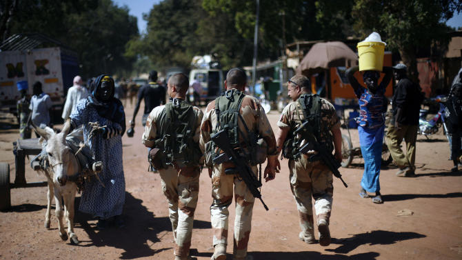 French troops walk in Niono, some 400 kilometers (249 miles) north of the capital Bamako Sunday Jan. 20, 2013. The Malian military announced late Saturday that the government was now controlling Diabaly, marking an important accomplishment for the French-led offensive to oust the extremists from northern and central Mali. (AP Photo/Jerome Delay)
