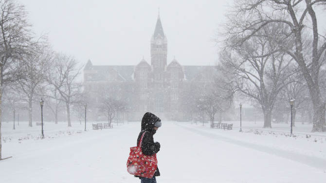 A student makes her way across the campus of Friends University in Wichita, Kan. as heavy snow falls on Wednesday morning, Feb. 20, 2013. A large winter storm moved in over the early morning hours and is expected to last until Thursday evening. (AP Photo/The Wichita Eagle, Travis Heying)