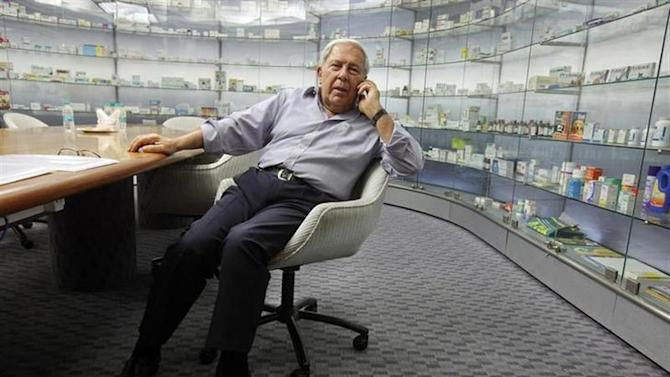 Y.K. Hamied, chairman and managing director of Indian generic drugmaker Cipla, speaks on his mobile phone in front of cabinets containing the company's products before an interview in Mumbai May 8, 2012. REUTERS/Vivek Prakash/Files