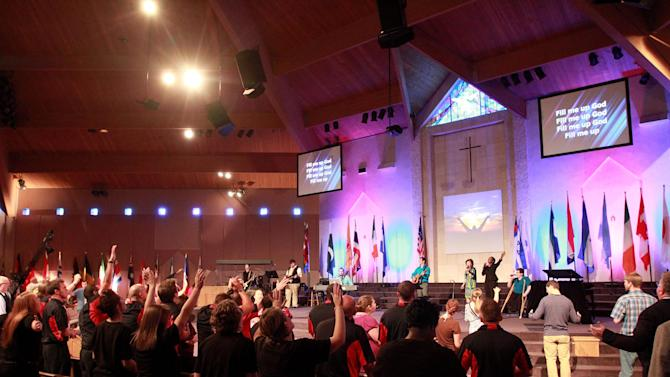 In this March 25, 2012, photo, the congregation at the Brownsville Assembly sing praises during service in Pensacola, Fla. The church that was home to the largest Pentecostal outpouring in U.S. history is on the edge of financial ruin. The revival that drew some 5,500 people nightly at its height saddled the congregation with an $11.5 million debt that members were left to pay off after both the out-of-town throngs and former Rev. John Kilpatrick moved on. The red ink is mostly unknown outside the congregation. (AP Photo/John David Mercer)