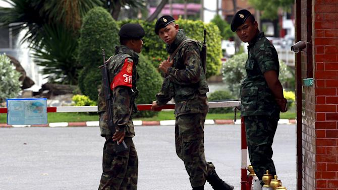 Thai Army officers stand guard at a gate of the military barracks believed to be holding two arrested bomb suspects involved in the recent Bangkok blast in Bangkok