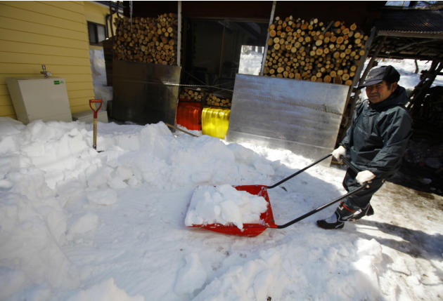 In this Monday, March 3, 2014 photo, Kunio Kikuchi, who is hearing impaired, shovels snow at Huck's House, a vocational center for the disabled in Tanohata, northeastern Japan. Kikuchi does chores