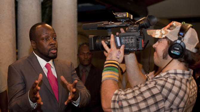 Haitian-born singer Wyclef Jean talks with a videojournalist after a press conference announcing his support on Haiti's presidential candidate Michel Martelly's run for the presidency in Port-au-Prince, Haiti, Wednesday, Feb. 16, 2011. (AP Photo/Ramon Espinosa)