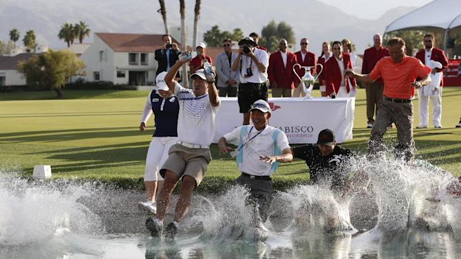 Inbee Park, left, of South Korea, celebrates by jumping into Poppy's Pond with friends and family after winning the LPGA Kraft Nabisco Championship golf tournament in Rancho Mirage, Calif., Sunday, April 7, 2013. (AP Photo/Chris Carlson)