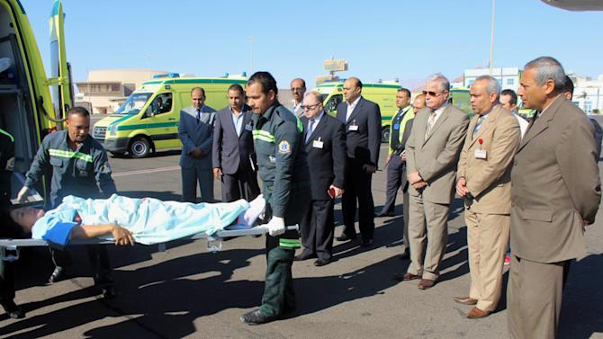 In this photo released by the Office of the South Sinai Governor, the Governor of South Sinai, Major General Khaled Foda, third right, and other officials watch as a South Korean tourist who was wounded in a deadly blast Sunday, on a bus in Taba, is evacuated to her home country, at Sharm el Sheikh airport, Egypt, Wednesday, Feb. 19, 2014. The bombing Sunday was the first targeting foreign tourists in the Sinai in nearly decade, raising fears that Islamic militants who have been waging a campaign of violence against security forces in the peninsula are now turning to attack tourism, a pillar of Egypt's economy. (AP Photo/Office of the South Sinai Governor)