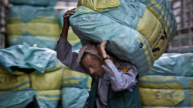 In this photo taken on Tuesday, Dec. 18, 2012, Yemeni worker, Afeef Yahya, 42, who earns 500 YR ($2.33 cents) per day, carries clothes for stock to a shop at a market in Sanaa, Yemen. According to recent government and international reports, unemployment in Yemen has risen to around 30 percent, and even 60 percent among the young. Around 54 percent of the population lives under the poverty, less than $2 per day. The unemployment rate has increased because of the political crisis and the popular uprising in 2011, forcing many factories, private enterprises, and establishments to shut down. (AP Photo/Hani Mohammed)