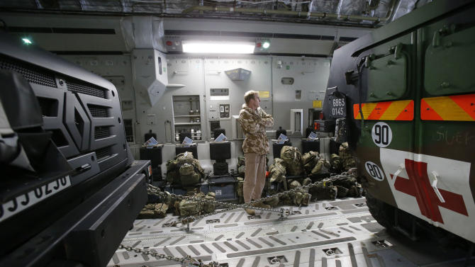 A British pilot stands between a French army truck and a medical armoured personnel carrier inside a British C17 transport plane prior to take off at the army base in Evreux, 90 kms(56 mls)north of Paris, Monday, Jan. 14, 2013. Britain over the weekend authorized sending two C-17 transport planes to help France bring more troops to Mali. The United States is sending drones, as well as communications and logistical support. (AP Photo/Michel Euler)