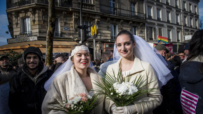 Women pose during a demonstration for the government project to legalize same-sex marriage and adoption for same-sex couples in Paris, France, Sunday, Jan. 27, 2013. (AP Photo/Benjamin Girette)