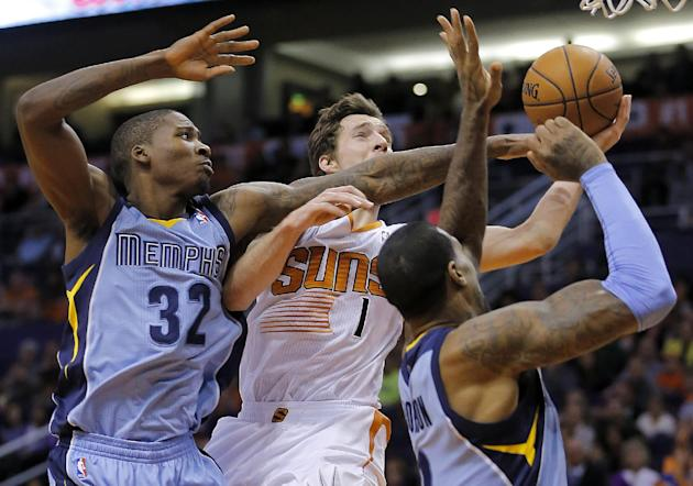 Phoenix Suns' Goran Dragic (1), of Slovenia, drives against Memphis Grizzlies' Ed Davis (32) and James Johnson during the second half of an NBA basketball game on Thursday, Jan. 2, 2014, in Ph