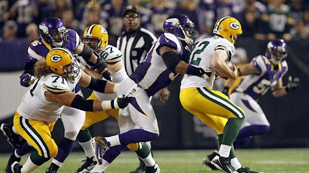 Green Bay Packers quarterback Aaron Rodgers (12) is sacked by Minnesota Vikings defensive end Everson Griffen (C) past Packers guard Josh Sitton (71) during the first half of their NFL football game in Minneapolis