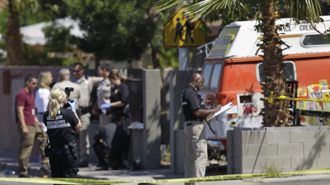 Crime scene investigators examine the scene of a home where two bodies and an injured man were found, Monday, April 16, 2012, in Las Vegas. Police are questioning a man covered in blood at the home where a 9-year-old boy told school officials his mother and sister were dead. (AP Photo/Julie Jacobson)