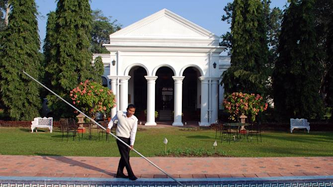 In this photo taken Nov. 29, 2012, a staff member cleans the pool of Thengal Manor, the gracious residence in Assam of one of India's most prominent tea dynasties in Jorhat, India. The manor, featuring superb food, service and serenity, was opened to guests in 2000. Others in India and Sri Lanka offer visitors a chance to sample the lifestyle of tea planters and, of course, their brews. (AP Photo/Denis Gray)