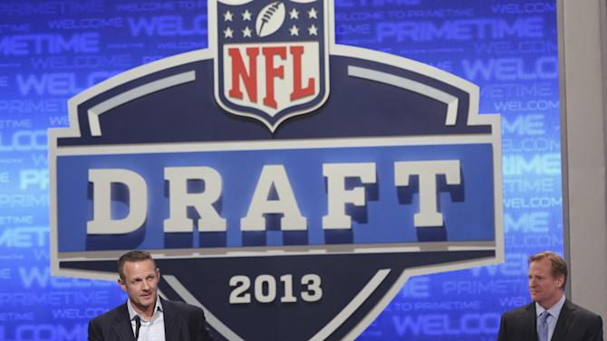 Former Pittsburgh Steelers running back Merril Hoge is joined by NFL commissioner Roger Goodell as he announces a draft pick during the second round of the NFL Draft, Friday, April 26, 2013 at Radio City Music Hall in New York.  (AP Photo/Mary Altaffer)