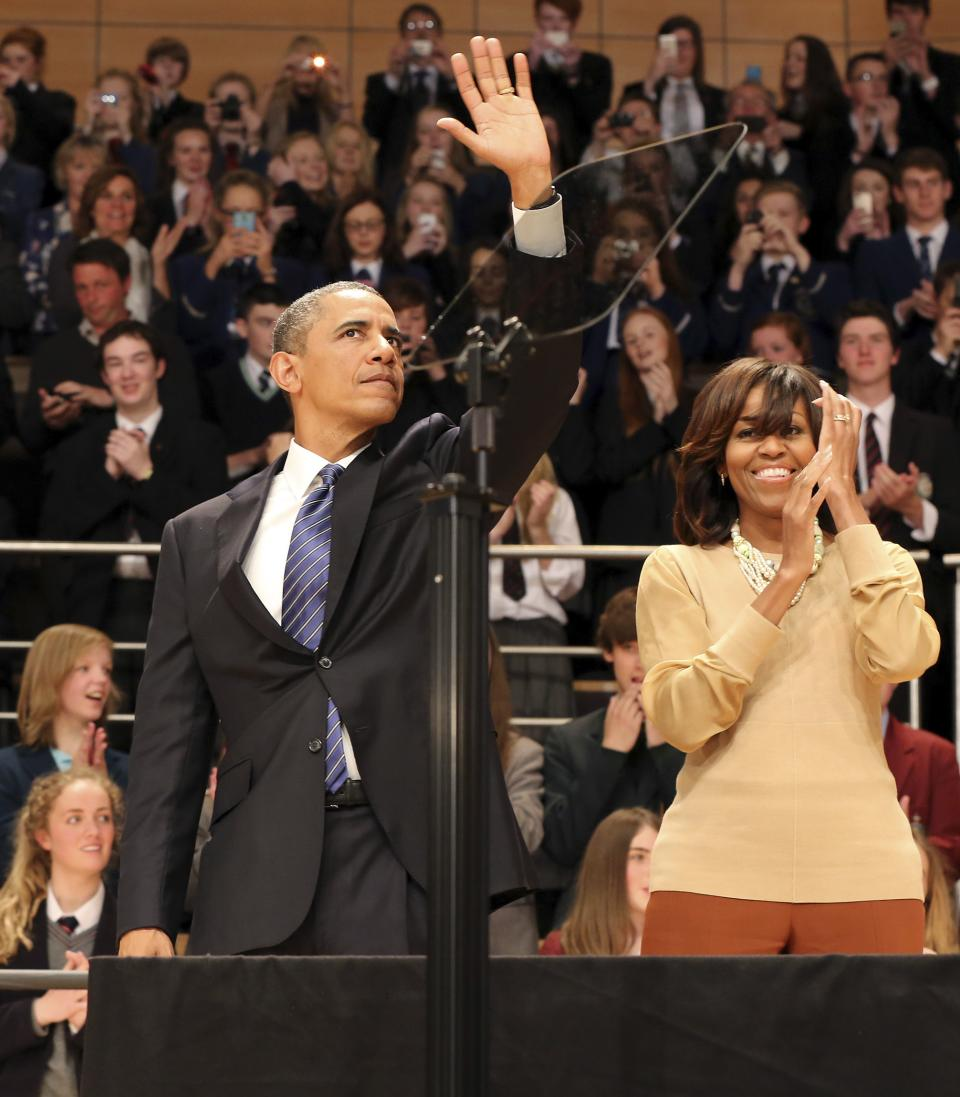 US President Barack Obama, left, and his wife Michelle Obama wave after he delivered a keynote address ahead of the G-8 summit at Waterfront Hall in Belfast, Northern Ireland on Monday, June 17, 2013. (AP Photo/ Paul Faith, Pool)