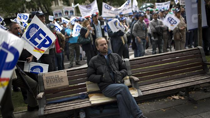 """Rumanian immigrant in Spain Sorin Bedreaga, 38, sits on a bench where he says he has spent 40 days on a hunger strike, as police officers protest by blocking the street in front of the Interior Ministry in Madrid, Spain, Saturday, Oct. 27, 2012. The demonstrators were protesting the government's austerity measures, especially the elimination of their Christmas bonus pay, one of 14 paychecks that most Spanish civil servants get each year. The placard next to Sorin reads in Spanish """"Hunger strike since 17 September 2012"""". (AP Photo/Emilio Morenatti)"""