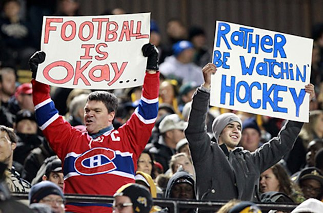 Fans holds signs commenting on the NHL lockout (Canadian Press)