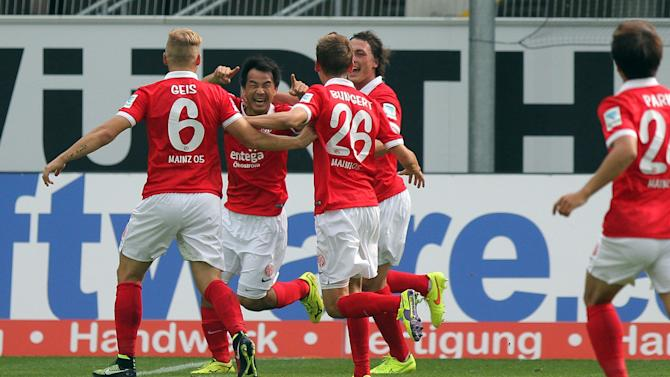 Mainz's Shinji Okazaki , second left, celebrates the opening goal during the German Bundesliga soccer match between SC Paderborn and. FSV Mainz 05 in Paderborn, Germany, Sunday Aug. 24, 2014. Mainz earned a 2-2 draw at promoted Paderborn with an injury time penalty to deny the home side a victory in its first Bundesliga game on Sunday. (AP Photo/dpa, Oliver Krato)
