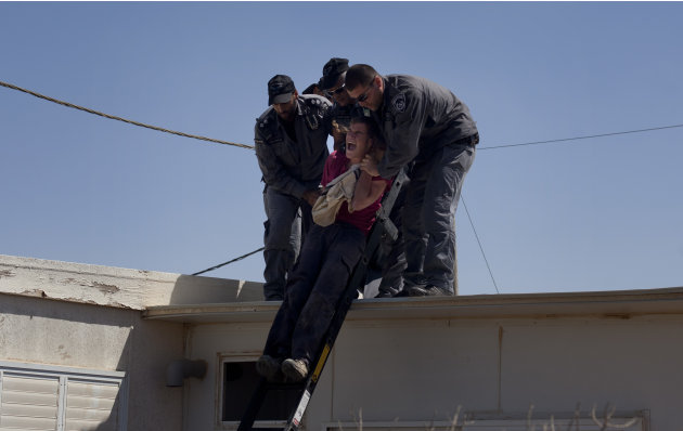 Israeli police officers evacuate a Jewish settler from the roof of a structure in the unauthorized West Bank Jewish settlement of Migron. Sunday, Sept. 2, 2012. Israel completed evacuation of Migron, 