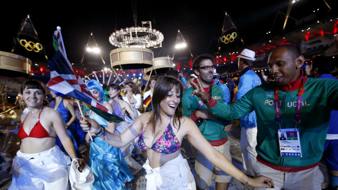Portugal's Nuno Delgado, right, dances with performers during the Closing Ceremony at the 2012 Summer Olympics, Monday, Aug. 13, 2012, in London. (AP Photo/Jae C. Hong)