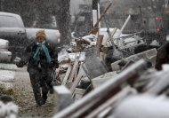 FILE - In this Nov. 7, 2012, file photo, a woman, who did not want to give her name, returns home from work in the snow to her house in the New Dorp section of Staten Island, New York. Residents of New York's Staten Island borough are noticing something new as they and volunteers work to clear the remains of storm-damaged homes: gawkers. Cruising by in cars or walking through streets snapping photos, these are people drawn to the scene of a tragedy to glimpse what they've seen on television come to life. (AP Photo/Seth Wenig, File)