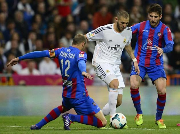 Real Madrid's French forward Karim Benzema (C) vies with Levante's defender Juanfran (L) and Greek defender Nikos Karampelas at the Santiago Bernabeu stadium in Madrid on March 9, 2014