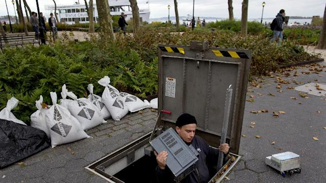 A technician with the Battery Conservancy removes below-ground fountain operation equipment near the water's edge at Battery Park in New York, Sunday, Oct. 28, 2012. Areas in the Northeast are preparing for the arrival of Hurricane Sandy and a possible flooding storm surge. (AP Photo/Craig Ruttle)