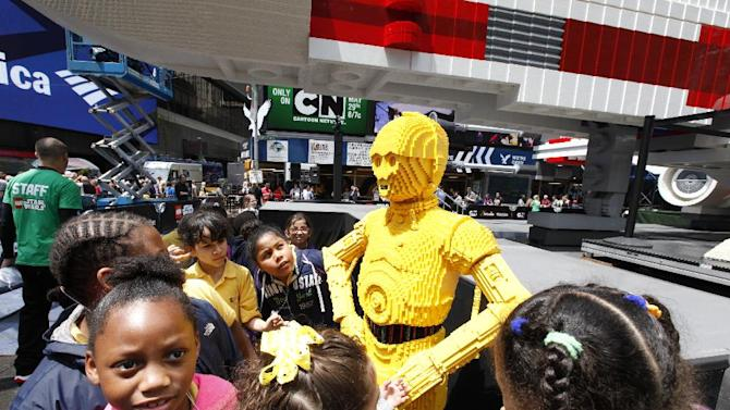 Visitors are seen after the unveiling to the world's largest LEGO Model, a 1:1 replica of the LEGO Star Wars X-wing Starfighter that took 32 Model Builders, 5.3 million LEGO bricks and over 17,000 hours to complete, in New York City's Times Square, Thursday May 23, 2013. (Amy Sussman/AP Images for The LEGO Group)