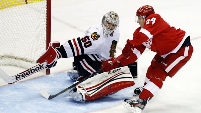 Chicago Blackhawks goalie Corey Crawford (50) deflects a shot by Detroit Red Wings center Damien Brunner (24) during the shootout of an NHL hockey game, Sunday, March 3, 2013, in Detroit. The Blackhawks won 2-1. (AP Photo/Duane Burleson)