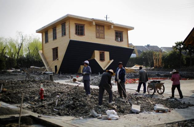Labourers work at upside-down house under construction at Fengjing Ancient Town, Jinshan District