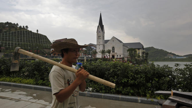 A worker walks at an European-style houses in Hallstatt See, a replica of Austrian town of Hallstatt, in Boluo county, Huizhou city, south China's Guangdong province Saturday, June 2, 2012. A group of Austrians whose scenic mountain village has been copied down to the statues by a Chinese developer attended Saturday's opening in China for the high-end residential project but were still miffed about how the company did it. The original is a centuries-old village of 900 people and a UNESCO heritage site that survives on tourism. The copycat is a housing estate that thrives on China's new rich. In a China famous for pirated products, the replica Hallstatt sets a new standard. (AP Photo/Vincent Yu)